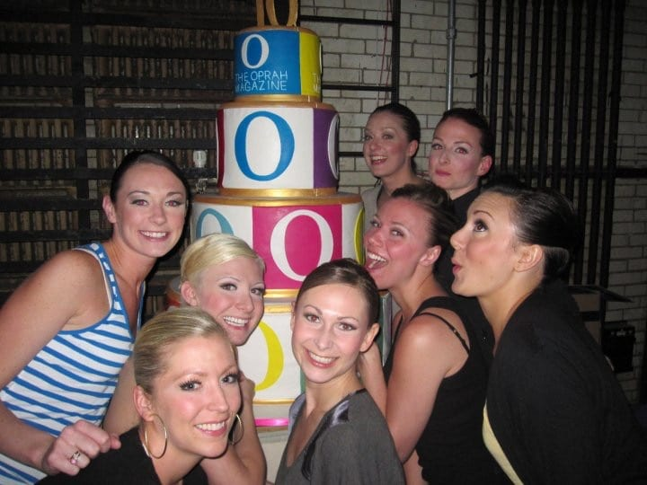 Sarah (the middle one on the left) and her Rockette sisters posing alongside Oprah's 4-tiered cake.