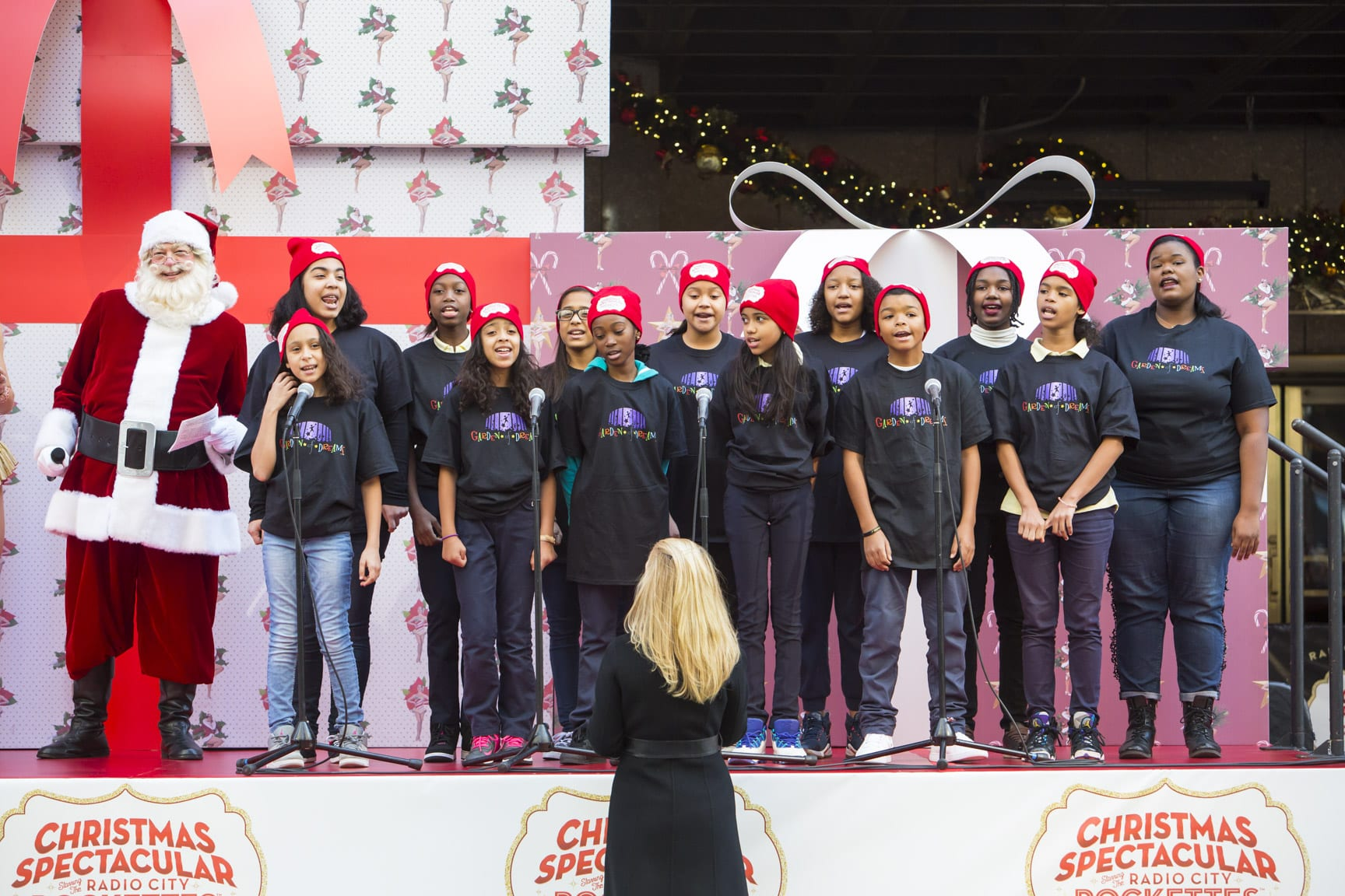 November 16, 2016: The Radio City Rockettes and Santa are joined by girls from the Garden of Dreams Foundation to sing on a float outside of Radio City Music Hall in New York City.